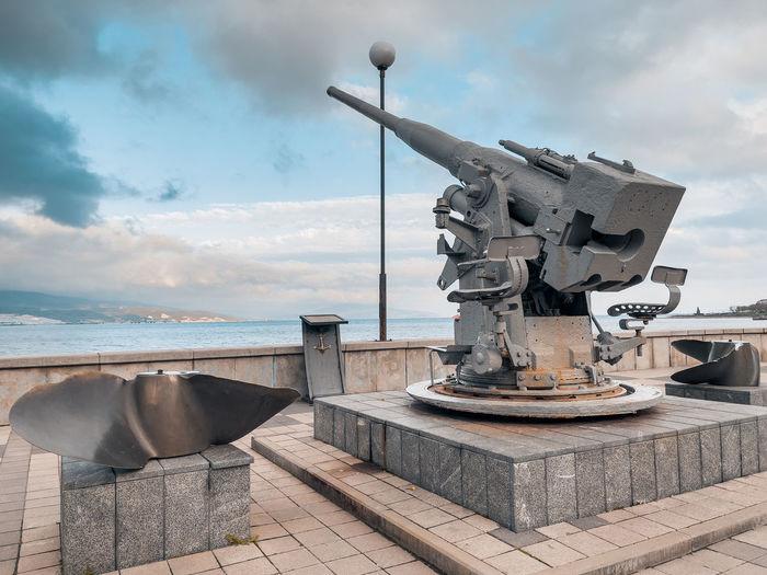 Sculpture on railing against sea