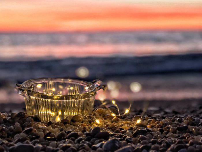 Close-Up Of Illuminated String Light At Beach During Sunset