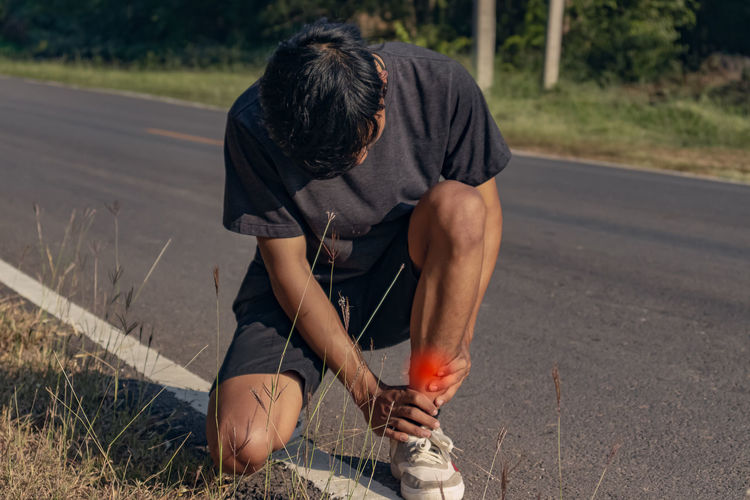 Rear view of man sitting on road