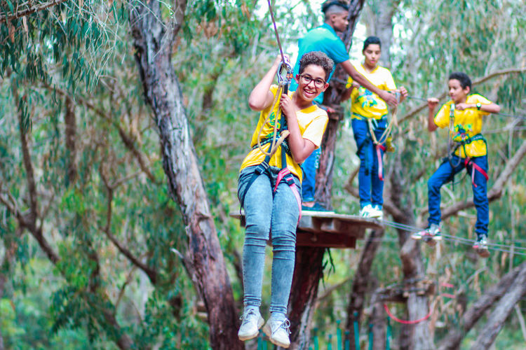 Holiday Suspended Ropes Suspension Bridge Tree Forest Happiness Smiling Plant Togetherness Leisure Activity Group Of People Emotion Land Casual Clothing Adult Fun Young Men Nature Full Length Young Adult Positive Emotion Outdoors Travel