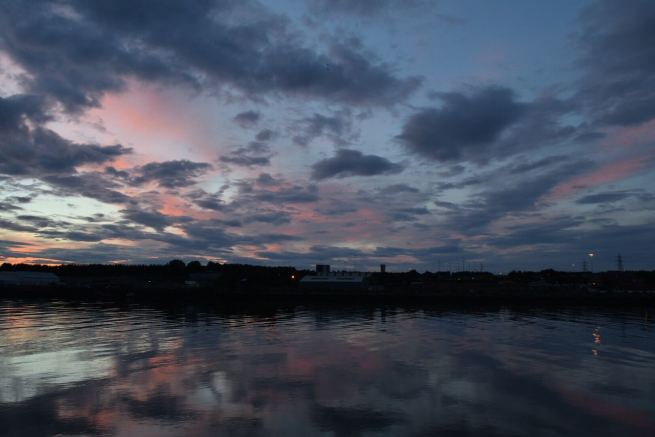 sky, cloud - sky, water, sunset, reflection, no people, river, dramatic sky, nature, beauty in nature, tranquility, scenics, built structure, outdoors, building exterior, dusk, architecture, waterfront, tranquil scene, silhouette, city, tree, cityscape, day