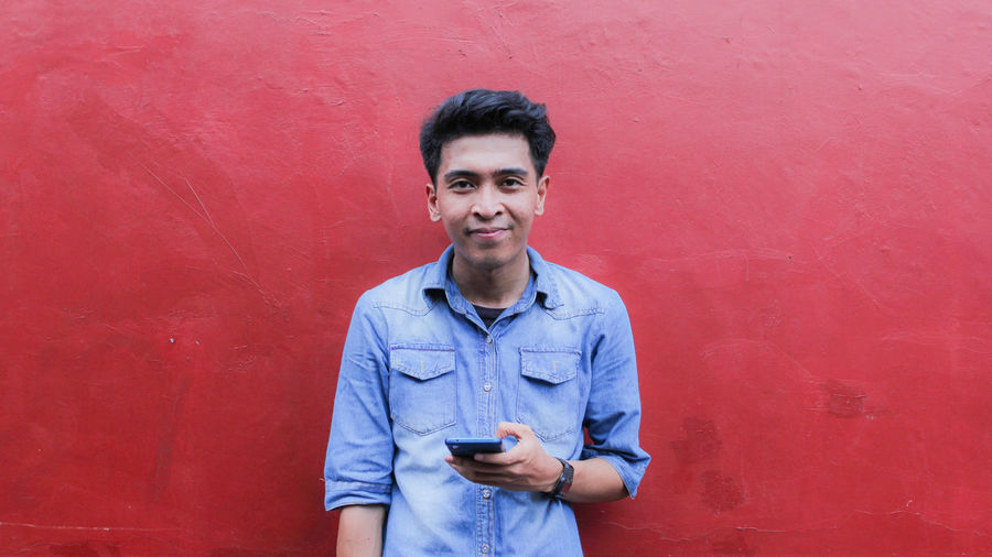 Portrait of smiling young man standing against red wall