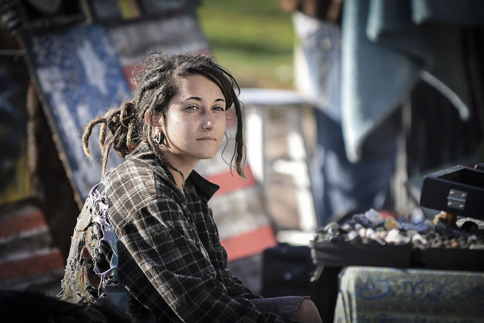 Deep In Thought Hippy Lifestyles Neglected Architecture Pensive Person Plaid Portrait Rasta Girl Reflective Soft Lighting Street Art Street Merchants Street Photogtraphy Street Shop Sun Lit Thousand Yard Stare Torn Clothing Up Close Street Photography Venice Beach
