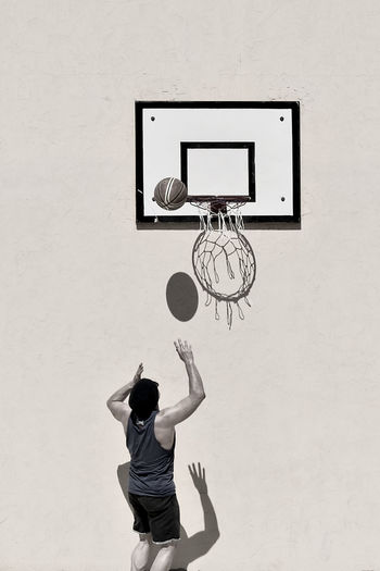 Rear View Of Man Playing Basketball