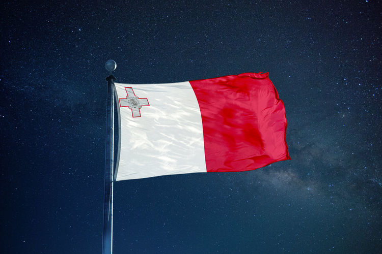 Low angle view of maltese flag against star field sky