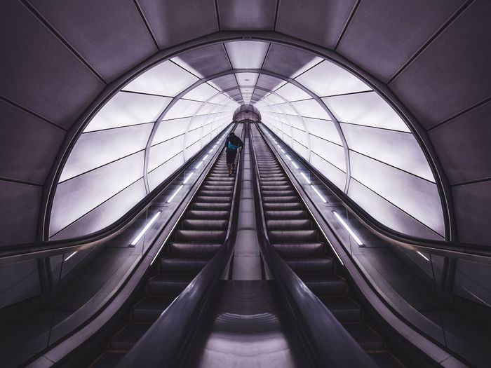 Rear view of man standing on escalator at subway station