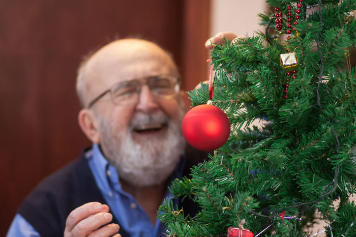 happy old man putting ornaments on Christmas tree Family Holiday Joyful Man Bald Beard Celebrate Celebration Christmas Christmas Decoration Close-up Eyeglasses  Festive Gift Grandpa Happiness Home Interior Indoors  Lifestyles Old Pensioner People Portrait Senior Adult Tree