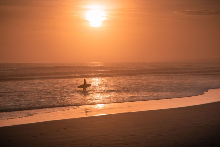 The beach of Mejia. Mejia Beach Sand Outdoors Water Nature South America Latin America Explore Surf Sport Sunset Sea Land Real People Silhouette Leisure Activity Sun Scenics - Nature Beauty In Nature Footsteps Surfboard Moody Sky Non-urban Scene Remote One Person Lifestyle