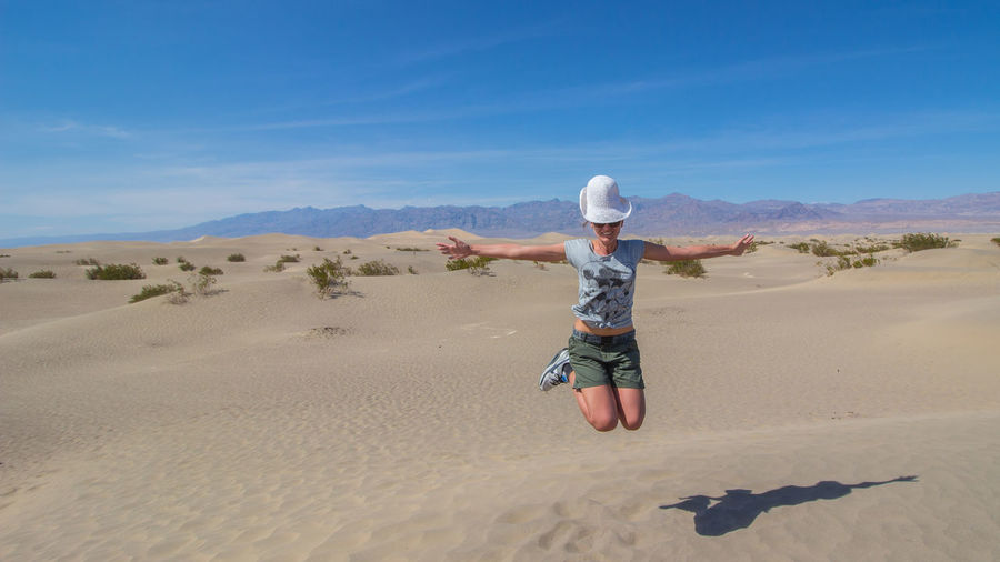 Full length of woman with arms outstretched jumping at desert against sky