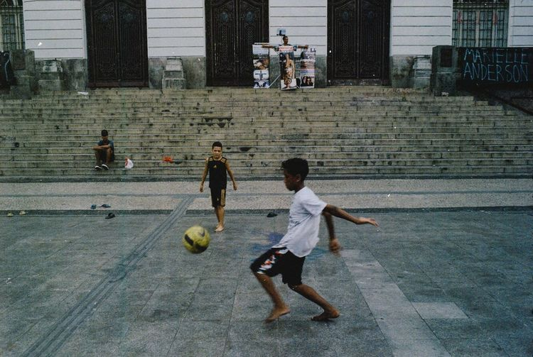 Group of people playing soccer ball on field