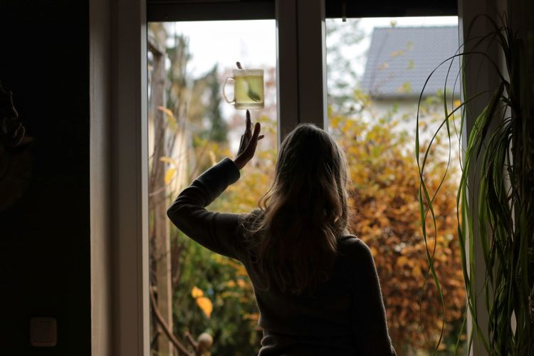 Rear view of woman with tea cup against window