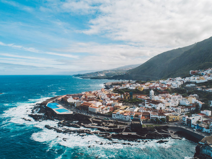 Aerial view of sea and buildings against sky