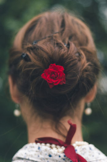 Red Rose In Hair Bun Of Woman