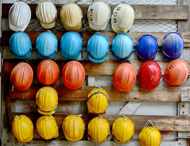 Multi Colored Helmets Hanging On Wooden Wall