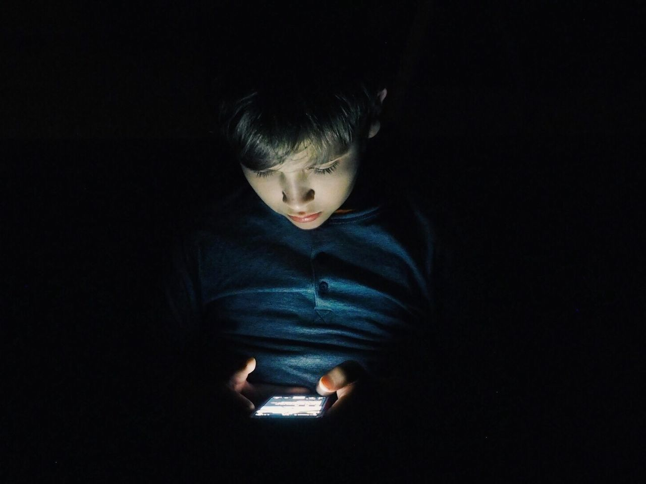CLOSE-UP OF BOY IN ILLUMINATED DARKROOM