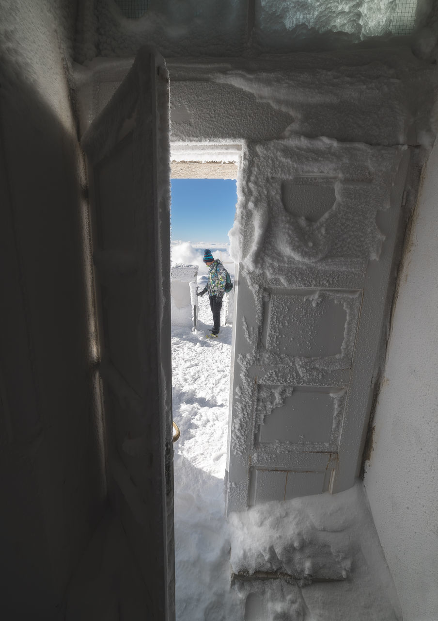 winter, snow, cold temperature, window, real people, one person, day, men, indoors, adventure, nature, full length, sky, people