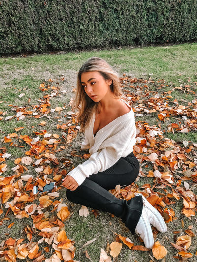 Young woman in autumn leaves on field