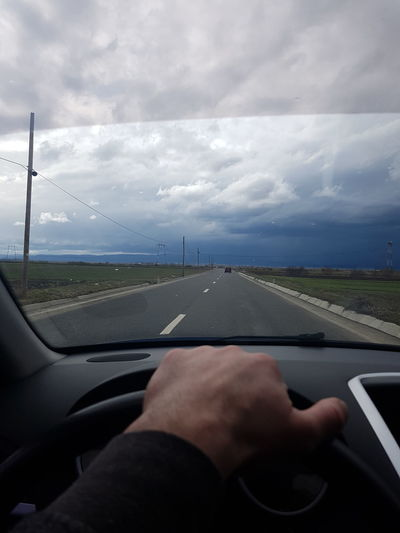 Car Car Interior Cloud - Sky Finger Glass - Material Hand Human Body Part Human Hand Land Vehicle Mode Of Transportation Motor Vehicle Nature One Person Outdoors Real People Road Road Trip Sky Transparent Transportation Travel Vehicle Interior Windshield