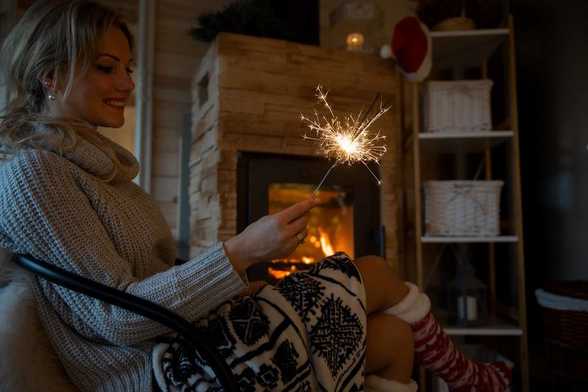 Woman sitting by fireplace and holding sparklers in cozy mountain cabin Woman Sitting Fireplace Holding Sparkle Sparkler Sparklers Cozy Cabin Life Winter Wintertime Holiday Holidays Season  Christmas Moment New Year New Year Beginnings Socks Blanket Sexygirl Sexywomen