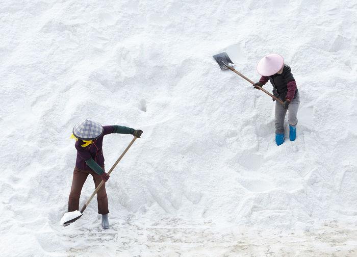 Full length of men cleaning snow with shovel