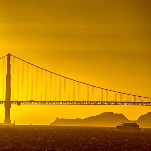 Scenic view of bridge over sea against orange sky