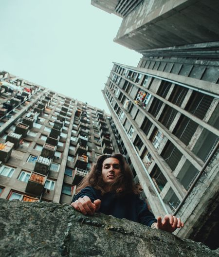 Portrait of young woman against building in city against clear sky