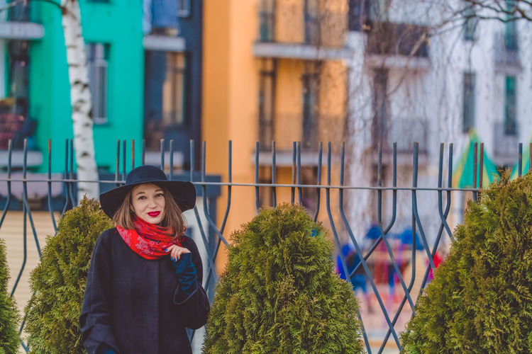 Portrait of woman wearing hat standing against fence in city