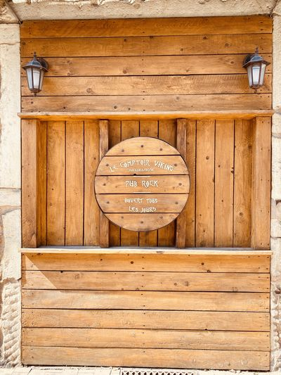 Close-up of sign on wooden wall