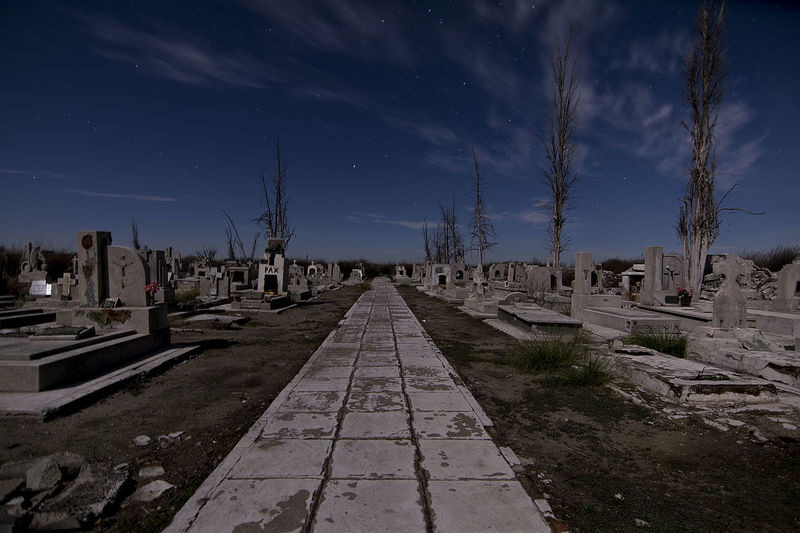 Footpath amidst gravestones in cemetery against sky at night