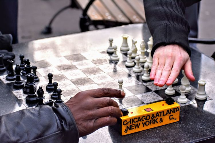 Cropped hands of friends playing chess