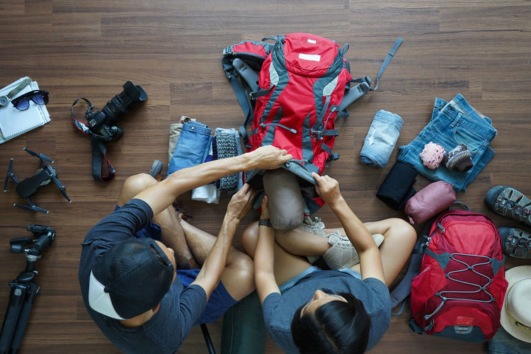 High Angle View Of People Packing Backpack On Hardwood Floor