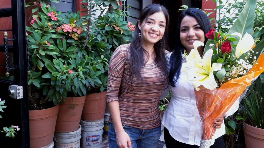 Portrait of smiling women with bouquet standing against potted plants