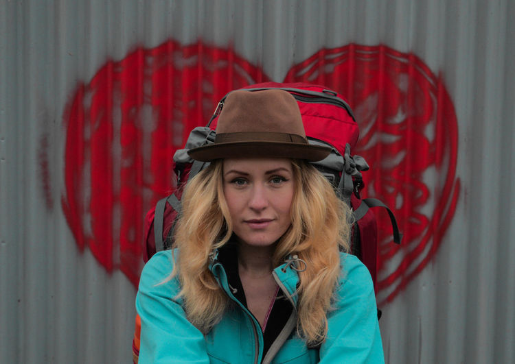 young caucasian woman backpacker standing in front of a wall with big red heart 20s Backpacking Blonde Bohemian Freedom Hiking Love Red Standing Travel Woman Adventure Background Backpacker Caucasian Face Female Free Spirit Gap Year Girl Headshot Heart Portrait Traveler
