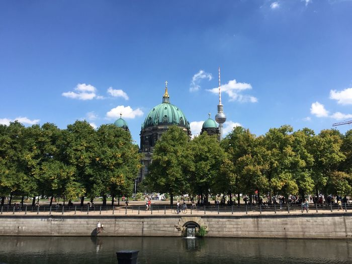 Church and fernsehturm by river in city against sky
