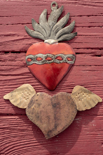 unique vintage hand-hammered copper and brass metal heart with wings and metal red heart form with silver tone chain and flames at top from Mexico Heart Shape Positive Emotion Love Emotion Wood - Material Close-up No People Creativity Directly Above Indoors  Design Still Life Table Red Art And Craft Valentine Hand Made Folk Art  Outsider Art Mexican Culture Art And Craft Love ♥ Metallic Metalwork
