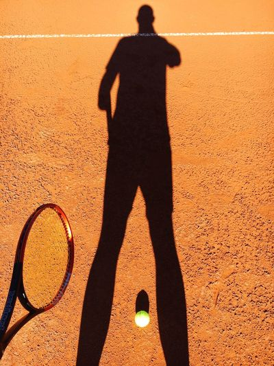 Shadow Of Tennis Player Falling On Field
