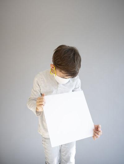 Full length of man holding paper against white background