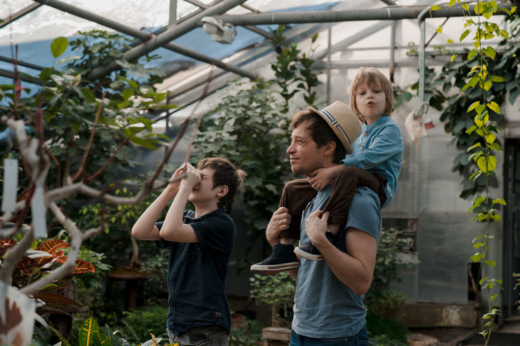 Adventurous family inspecting tropical gallery in botanical garden. local travel
