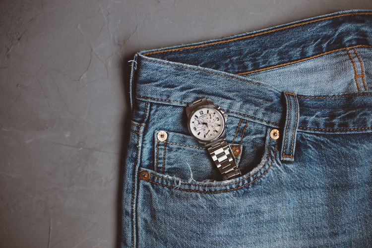 Women's trendy accessories, women's watch on bracelet and blue jeans on gray view.