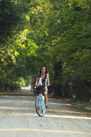 Woman cycling in a park of a city. City Exercise Summertime Transportation Woman Bicycle Cycling Girl Leisure Activity Lifestyles Mode Of Transport Nature Outdoors Park - Man Made Space Real People Ride Riding Smiling Summer Transportation Urban Urban Cycling Urban Transportation Young Adult