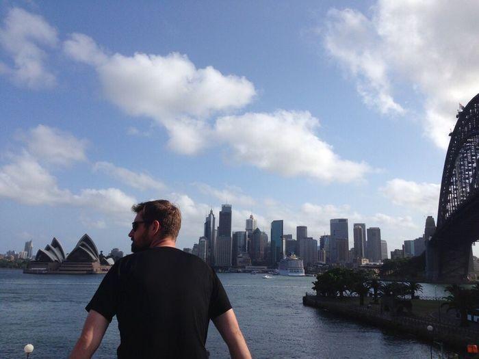 Rear view of man looking at sea by buildings against sky