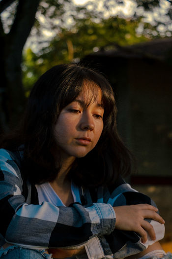 Close-up of sad woman sitting in park
