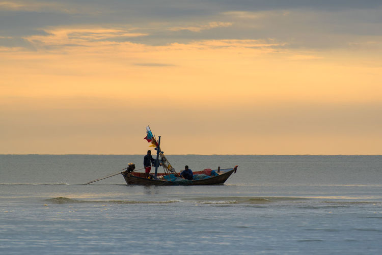 Man in boat at sea against sky during sunset