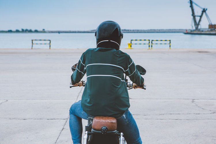 Rear view of man riding bicycle on sea