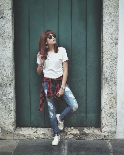 Young woman in sunglasses standing against door