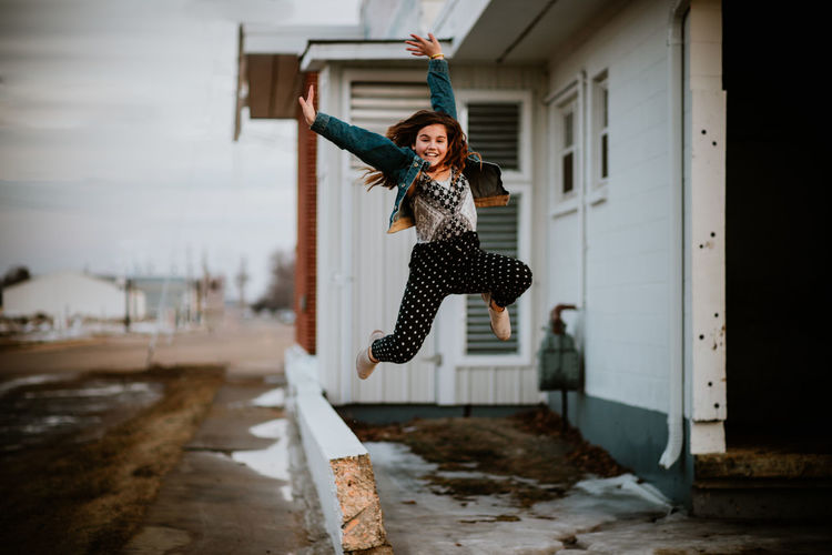 Woman jumping in front of built structure