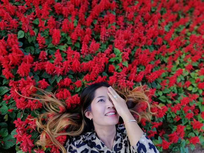 High angle view of woman relaxing amidst flowering plants
