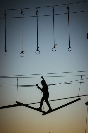 Low angle view of silhouette girl hanging on cable against sky