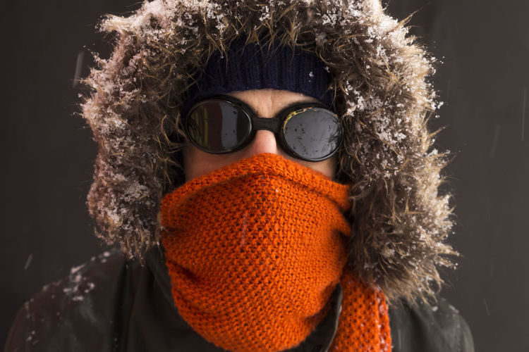 Portrait of a single male winter adventurer wearing a warm green coat with fur hood, a blue ski cap, an orange scarf and black retro style goggles Winter Warm Clothing Clothing One Person Headshot Portrait Adventure Wintertime Goggles Vintage Retro Styled Coat Fashion Man Adult Scarf Orange Color Outdoors Freezing Freezing Cold Exploration Polar Climate Snow Leisure Activity Close-up