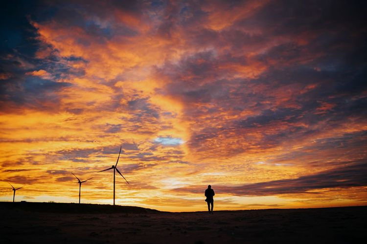 Silhouette man standing on land against cloudy sky during sunset